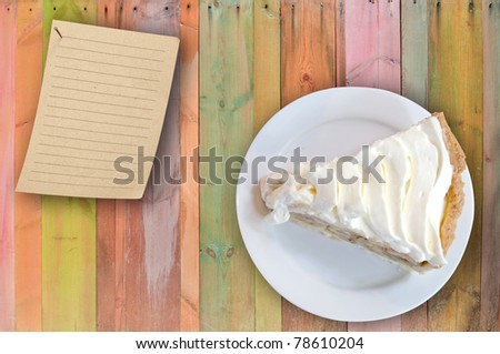 banana cream custard pie on colorful wooden table with note - stock photo
