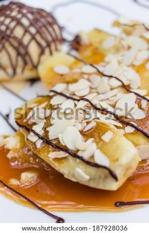 Banana crepe caramel with ice-cream on white plate - stock photo