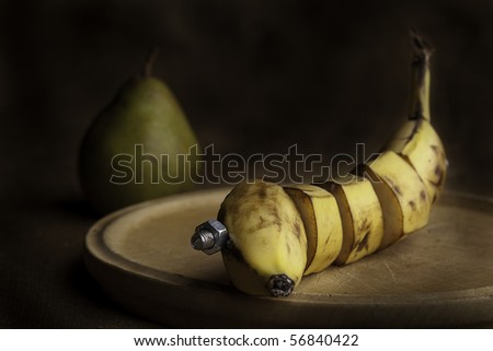 banana manipulated fruit with bolt holding it together - stock photo