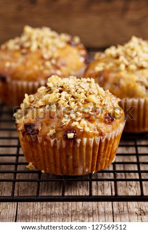 Banana muffins with walnuts and white chocolate on a cooling rack - stock photo