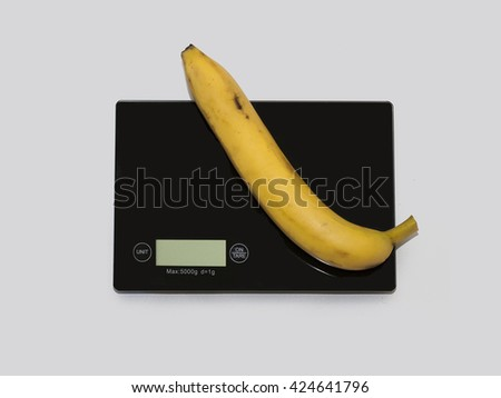 Banana on a digital white kitchen scale. (weighing products) - stock photo