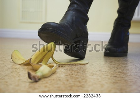 Banana skin lies ready to cause a painful slip-up. Slapstick concept illustrating danger and pitfalls. - stock photo
