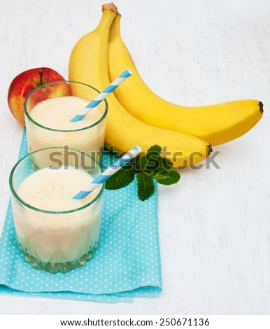 Banana smoothie and fruits on a wooden background
