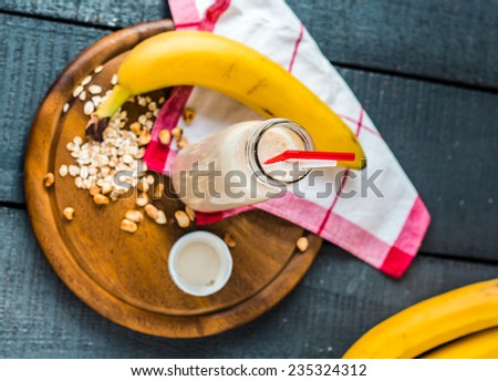 banana smoothie with oat flakes and milk in the bottle, breakfast,top view - stock photo