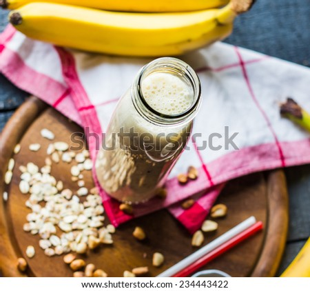 banana smoothie with oat flakes and milk in the bottle,healthy breakfast - stock photo