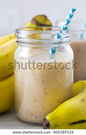 Banana smoothies on white wood background