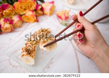 Banana sushi servered with nuts and granola on a glass plate. Hands with Japanese sticks. Woman eating healthy snack. Flowers and fruit breakfast or dessert. - stock photo