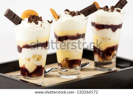 banana trifle parfaits in tall glasses decorated with cream, chocolate bar, chocolate shavings and vanilla wafers served on brown wooden tray with spoons - stock photo