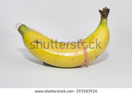 Banana with condom on white background - stock photo