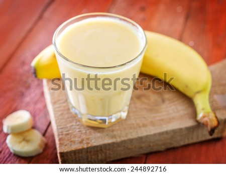 banana yogurt in glass and on a table - stock photo
