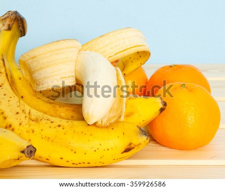 Bananas, mandarines on wooden table on blue background.