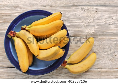 Bananas on blue plate and wooden background  - stock photo