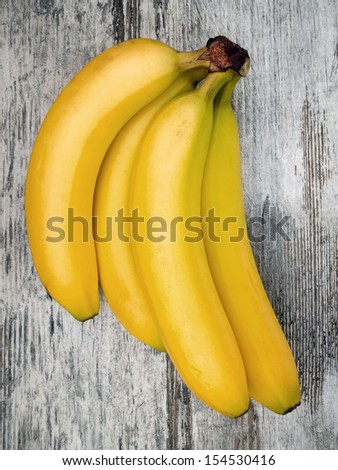 Bananas still life on wooden table, overhead view - stock photo