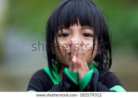 BANAUE, PHILIPPINES, DECEMBER 04 : A young unidentified Filipino little girl is praying under the rain in the village of Banaue, north Luzon, Philippines, on december 04, 2013 - stock photo