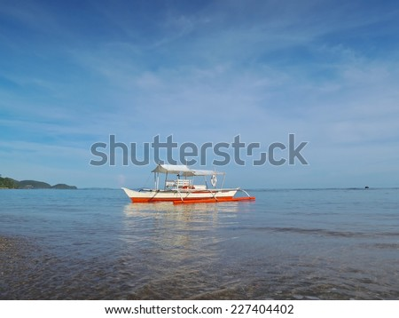 Banca boat rests on a tropical beach