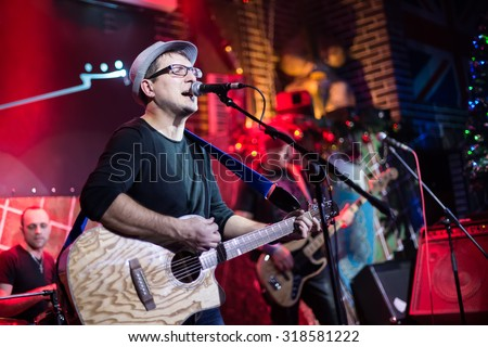 Band performs on stage, rock music concert. Warning - authentic shooting with high iso in challenging lighting conditions. A little bit grain and blurred motion effects. - stock photo