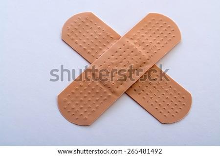 bandage cross on white background - stock photo