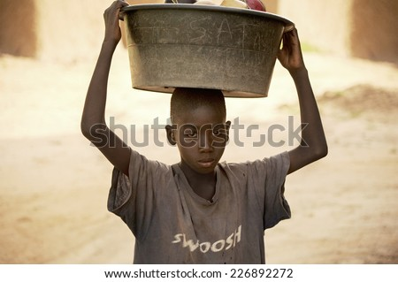 BANDIAGARA, MALI, AFRICA - AUGUST, 28, 2011 Dogon boy wearing kitchen utensils to wash in the river - stock photo