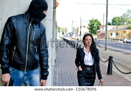 Bandit in mask with gun waiting for victim - stock photo