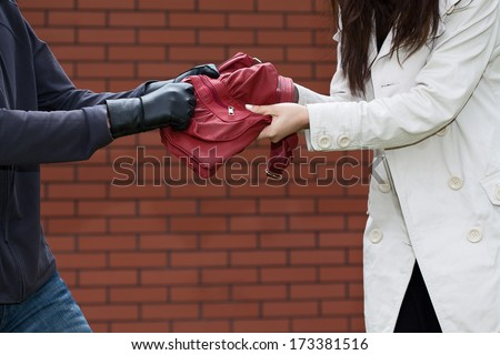 Bandit stealing a purse in dangerous district - stock photo