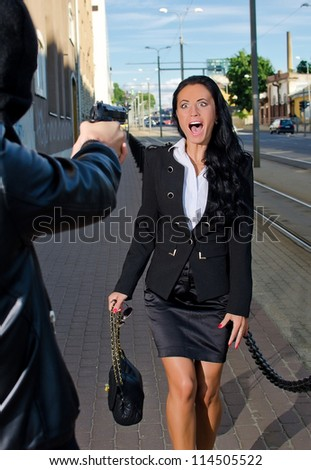 Bandit with a gun threatening young woman in the street - stock photo