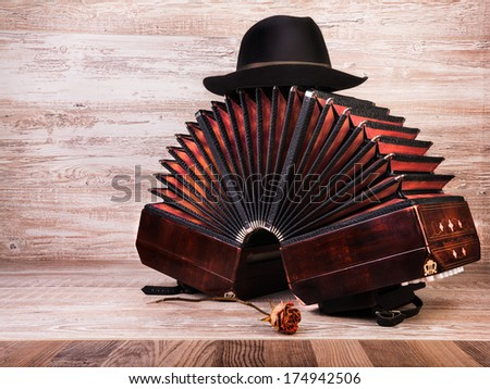 Bandoneon on wooden background with a male black hat on top, text space - stock photo