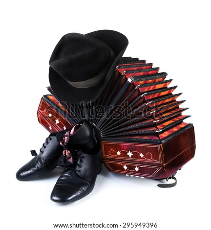 Bandoneon, pair of tango shoes, necktie and a black hat on white background - stock photo