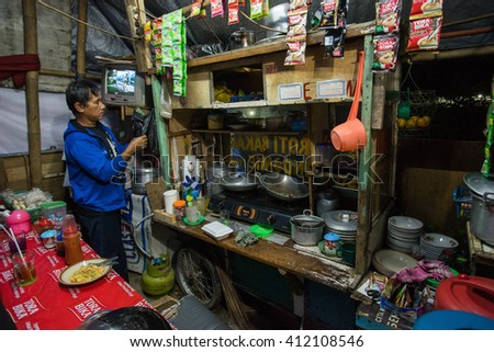 BANDUNG, INDONESIA - JANUARY 15 2016: Unidentified man cooking in his small food stall at night in Bandung, Indonesia. - stock photo