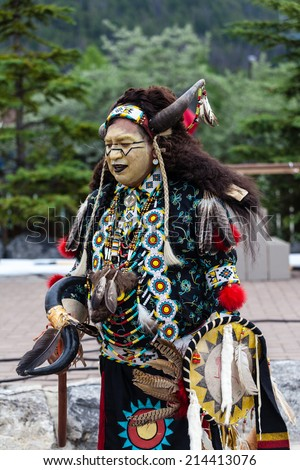 BANFF, CANADA - JUL 3: A native Blackfoot Indian chief wearing a split-horn bison bonnet dances during a performance at the Banff Summer Arts festival July 3, 2014.
