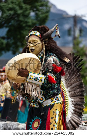 BANFF, CANADA - JUL 3: A native Blackfoot Indian chief wearing a split-horn bonnet dances during a performance at the Banff Summer Arts festival July 3, 2014.  - stock photo