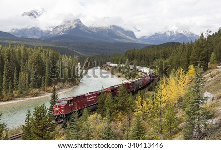BANFF NATIONAL PARK, CANADA - SEPTEMBER 18: Freight train moving along Bow river in Canadian Rockies on September 18, 2015 in, Banff national Park, Alberta, Canada  - stock photo