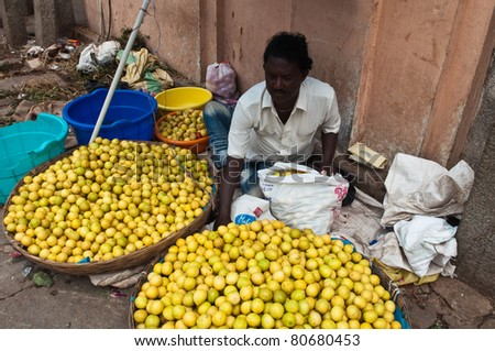 BANGALORE, IN - JUNE 26: Vendor sells limes on an unnamed street in Bangalore, IN June 26, 2011 in Bangalore, India. 42% of India falls below the international poverty line of $1.25 a day. - stock photo