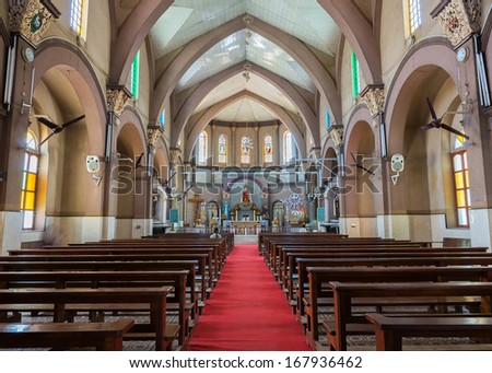 BANGALORE, INDIA - CIRCA OCTOBER 2013: A red carpet, flanked by brown benches, leads to the altar section of this little Catholic church in Bengaluru, with the statue of the Sacred Heart.