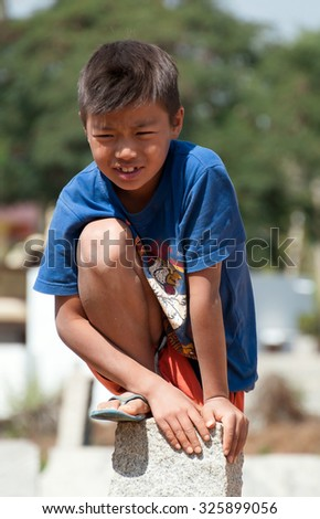 BANGALORE, INDIA - DEC 26, 2014: Unidentified Indian boy on stone pillar on the street in Bangalore.  Karnataka. India