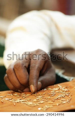 Bangalore, Karnataka, India - March 20, 2014: Unidentified man embroidering cloth in traditional Indian method using golden thread, zardosi embroidery of India