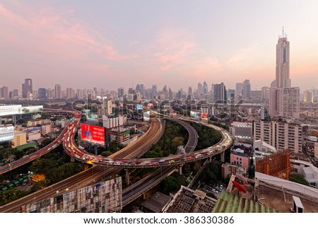 Bangkok at rosy dusk with skyscrapers in background and busy traffic on elevated expressways & circular interchanges ~ View of Bangkok City at rush hour with traffic jam on intertwined highway bridges - stock photo
