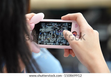 BANGKOK - AUG 17: A protester uses a smartphone to capture an anti-government rally on Aug 17, 2013 in Bangkok, Thailand. Protesters known as V for Thailand protested a controversial amnesty bill. - stock photo