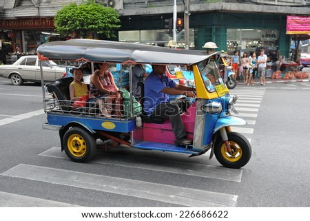 BANGKOK - AUG 2: A tuk tuk taxi transports passengers on a street in the Thai capital on Aug 2, 2012 in Bangkok, Thailand. Tuk tuks are an inexpensive means of transport with fares from $0.50 a trip. - stock photo
