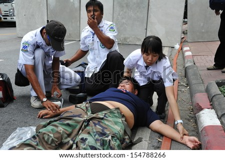 BANGKOK - AUG 7: An injured protester is treated by paramedics after collapsing during an anti-government rally near parliament on Aug 7, 2013 in Bangkok, Thailand.