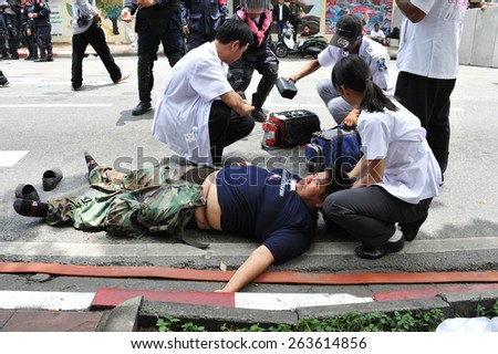 BANGKOK - AUG 7: An injured protester is treated by paramedics after collapsing during clashes at an anti government rally near the Thai parliament on Aug 7, 2013 in Bangkok, Thailand. - stock photo