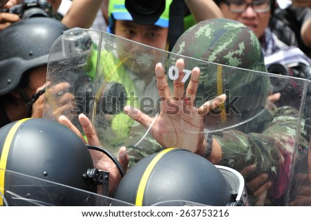 BANGKOK - AUG 7: Protesters supporting the Thai army confront riot police at a barricade near the Thai parliament during an anti government rally on Aug 7, 2013 in Bangkok, Thailand. - stock photo
