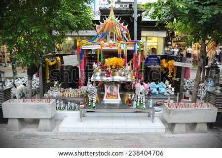 BANGKOK - AUG 7: View of a traditional Thai spirit house seen on a city centre street on Aug 7, 2012 in Bangkok, Thailand. Some Thais make offerings at spirit houses to bring merit and good fortune. - stock photo