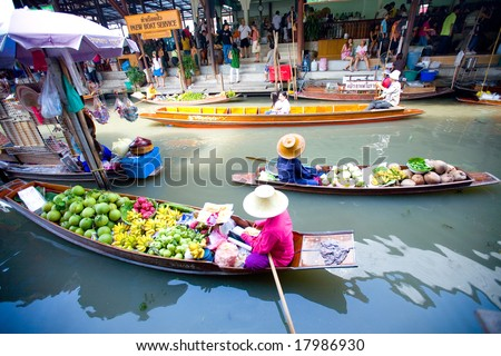 Bangkok August 2008. Busy sunday morning at Damnoen Saduak floating market. Locals selling fresh produce, cooked food and souvenirs while tourist waits of boats for hire. - stock photo