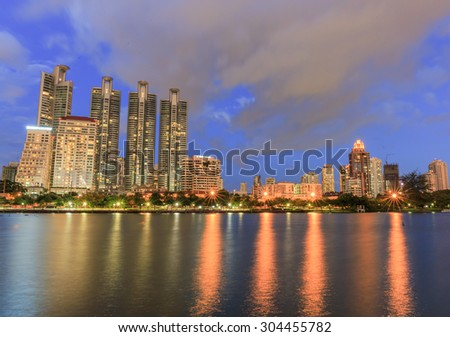 BANGKOK - AUGUST,9 : Cityscape view of modern buildings at Benjakitti garden at twilight time where have the light of the lamps shining on the pool and buildings.THAILAND AUGUST,9 2015 - stock photo