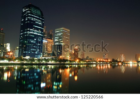 Bangkok cityscape of modern tower buildings with skyline reflection at Benjakitti park - stock photo