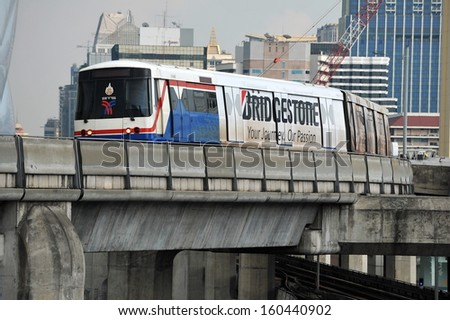BANGKOK - DEC 9:A BTS Skytrain on elevated rails above the city centre on Dec 9, 2012 in Bangkok, Thailand. Each train of the Thai mass public transport rail network can carry over 1,000 passengers.