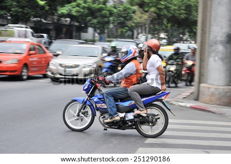 BANGKOK - DEC 17: A motorbike taxi transports a passenger on a city street on Dec 17, 2010 in Bangkok, Thailand. Motorbike taxis are a popular choice for the Thai capital's heavily congested roads. - stock photo