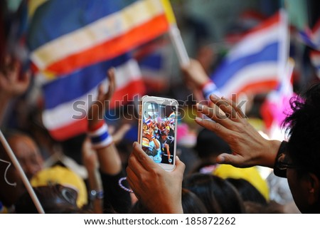 BANGKOK - DEC 20: A passerby uses a smartphone to capture a several thousand strong anti government street rally through the Thai capital's business district on Dec 20, 2013 in Bangkok, Thailand. - stock photo