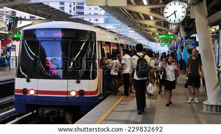 BANGKOK - DEC 3: Passengers board a BTS Skytrain at a city centre station on Dec 3, 2010 in Bangkok Thailand. The Thai capital's BTS rail public transport system serves 600,000 passengers daily. - stock photo