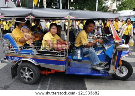 BANGKOK - DEC 5: Royalists ride a three wheeled tuk-tuk taxi after attending celebrations of the 85th birthday of Thai King Bhumibol Adulyadej on the Royal Plaza on Dec 5, 2012 in Bangkok, Thailand. - stock photo